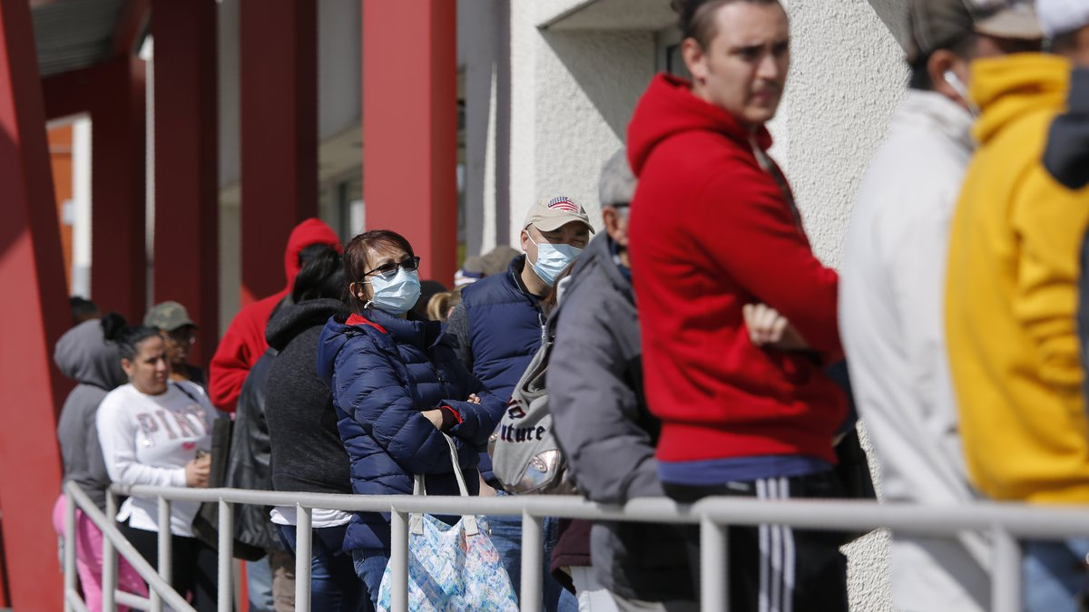 In this March 17, 2020 file photo, people wait in line for help with unemployment benefits at...