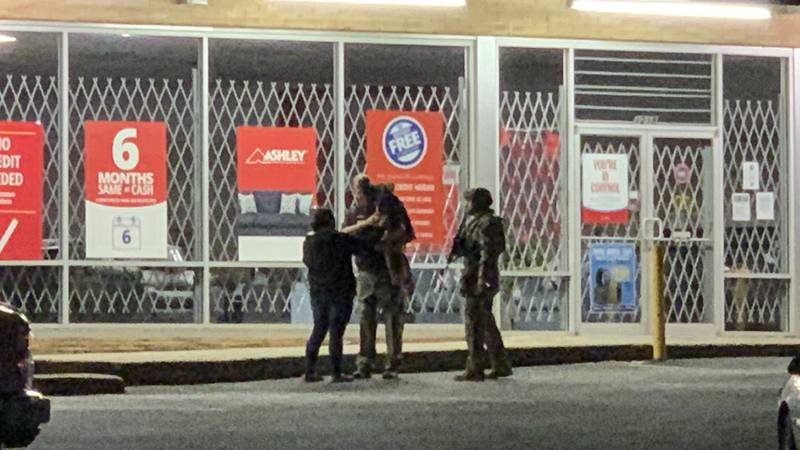 Tactical officers hand over child who was inside auto shop during multi-hour standoff.