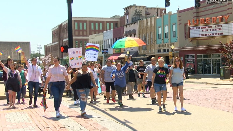 People walking, holding signs, and chanting during the Pride event in downtown on Sunday.