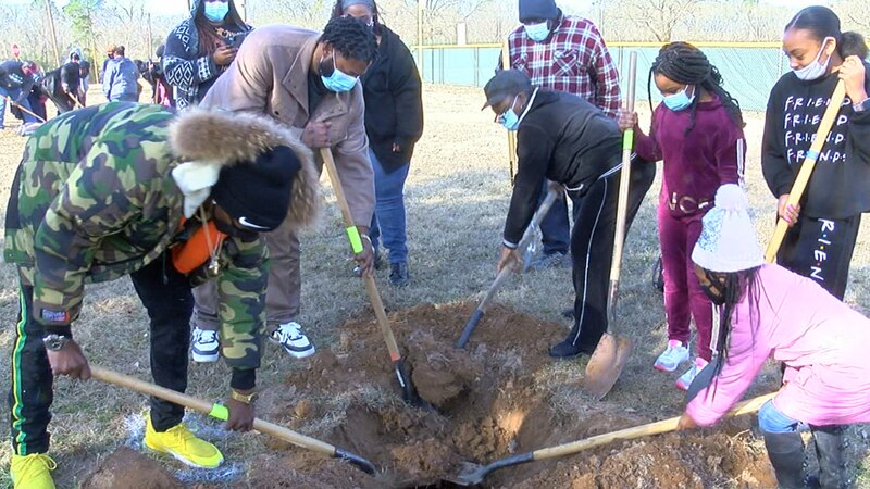 Family of the late Ed Moore dig into ground as they prepare to plant his tree.