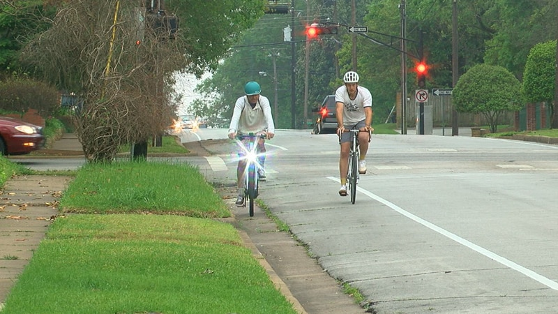 Bill Lewis and Asher Blair riding their bicycles in the new bikes lanes in the Azalea District.