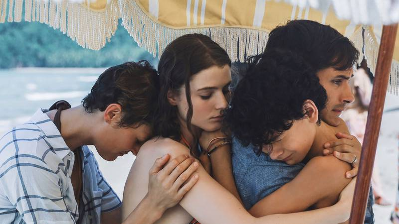 Prisca (Vicky Krieps, far left) and Guy (Gael Garcia Bernal, middle right) embrace their...