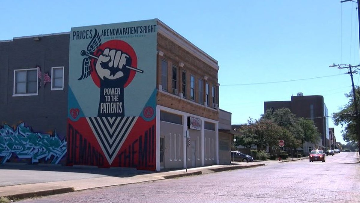 The Power to the Patients campaign mural can be seen on the side of Rudy's Barber Shop in...