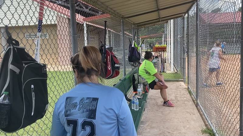Players sit in dug out at homerun for homeless event