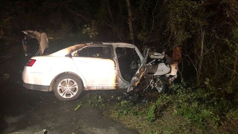 Passersby recued two people from a burning car after it went off the road and struck a tree in...