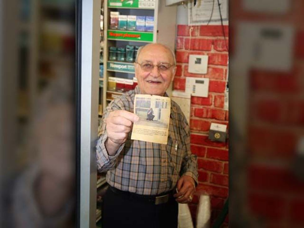 Papa Fatayri showing off newspaper clipping from another robbery, where he also shot the...