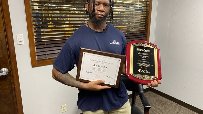Ronald Jordan posing with his nomination and WorkQuest Artie Lee Hinds Employee of the Year...