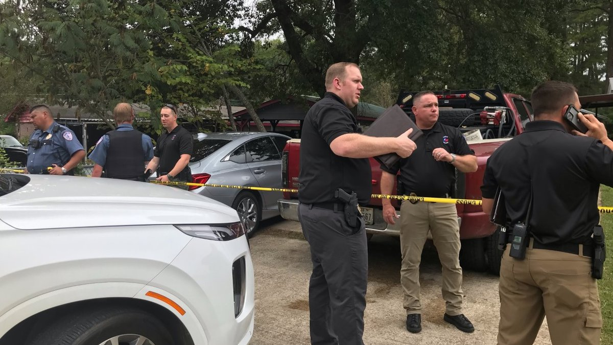 Lufkin police officers are seen outside a residence where a man and a woman were found dead...