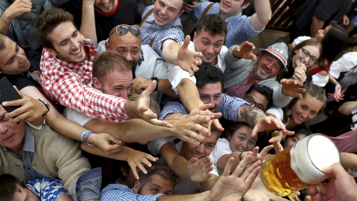 In this file photo dated Saturday, Sept. 21, 2019, people reach out for a glass of beer during...