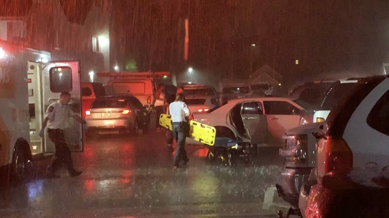 EMS treat victim in the back seat of a sedan before placing them on a stretcher.