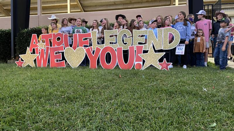 Members of Legend's Texas Junior High Rodeo Region 5 group gather in front of a sign outside...