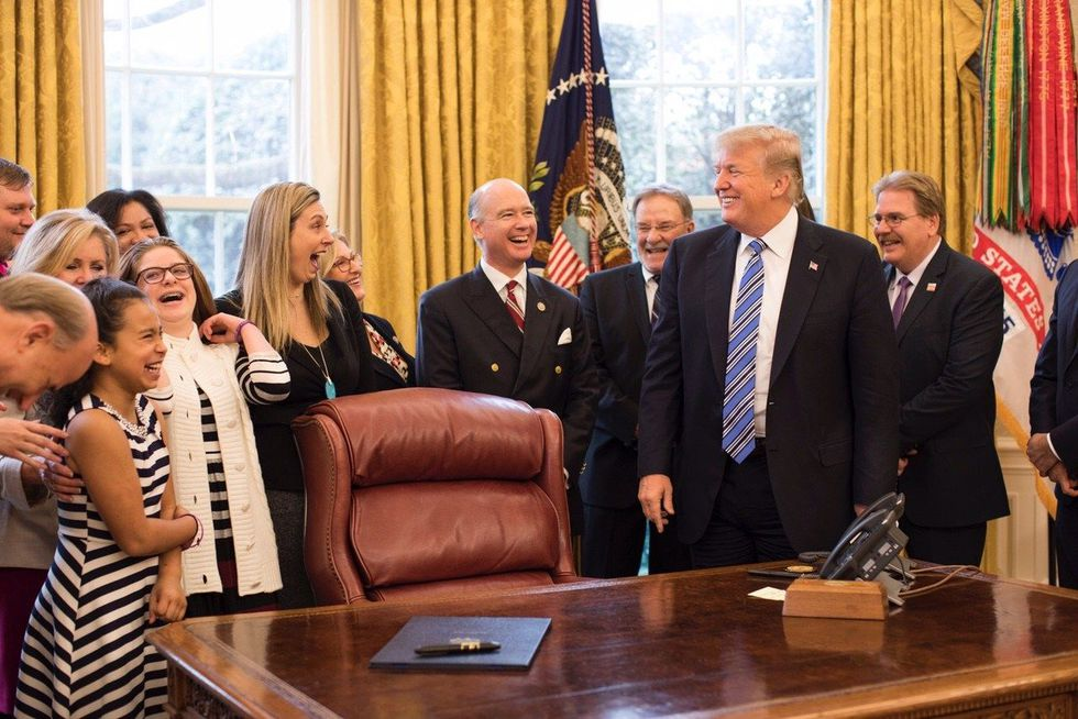 President Donald J. Trump signs Kari's Law in the Oval Office as Kari Hunt's family watches....
