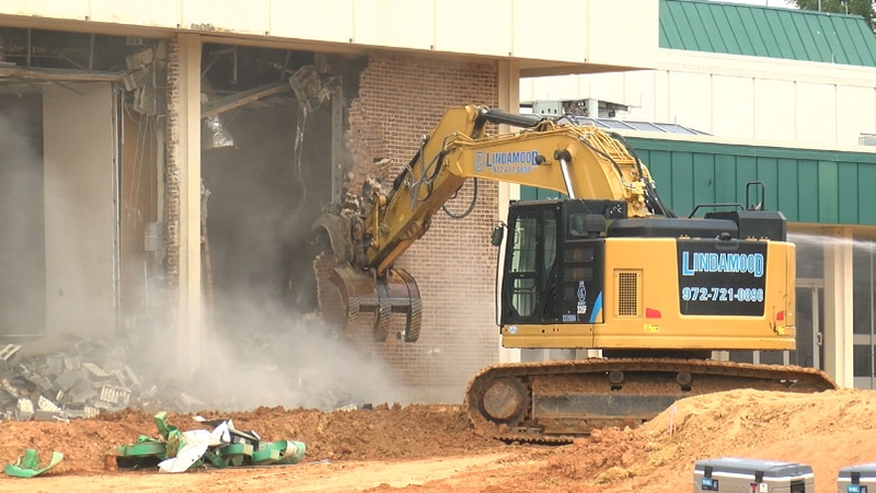 An excavator knocks down a wall of the Harvey Hall Convention Center for the first day of...
