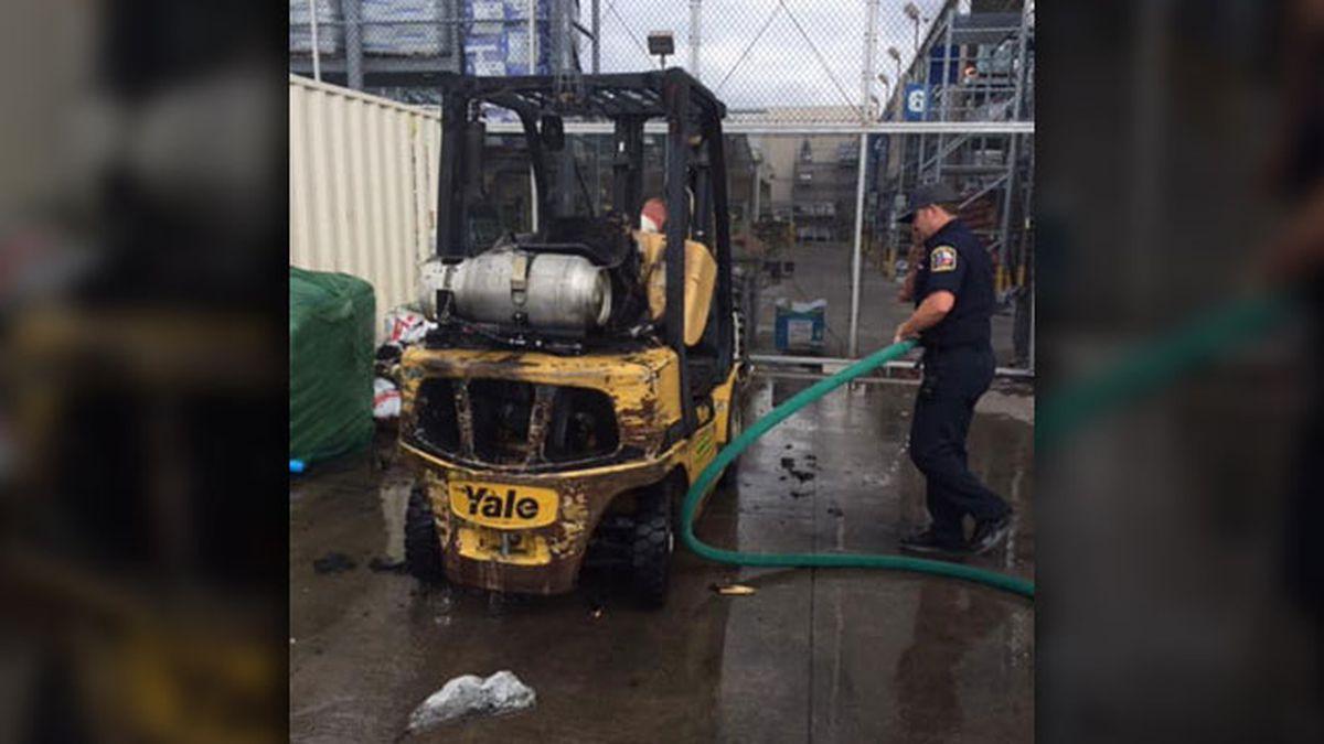 A Gun Barrel City firefighter moves a hose near a forklift that caught on fire Wednesday....