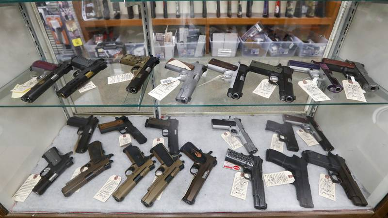 FILE - In this March 25, 2020 file photo, semi-automatic handguns are displayed at a shop in...