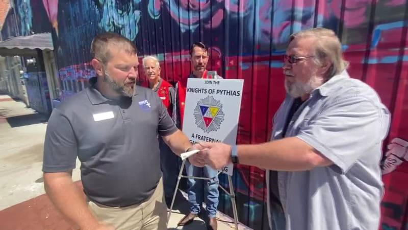 A member of the Longview chapter of the Knights of Pythias hands a check for $1,000 to Bryan...