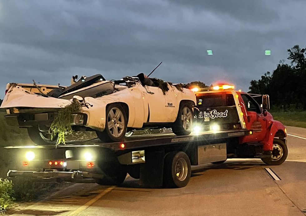 A wrecker hauls away the white pickup that was involved in a rollover wreck off the Lufkin loop...